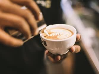 Ein Barista gießt Milchschaum in eine Tasse Cappucino